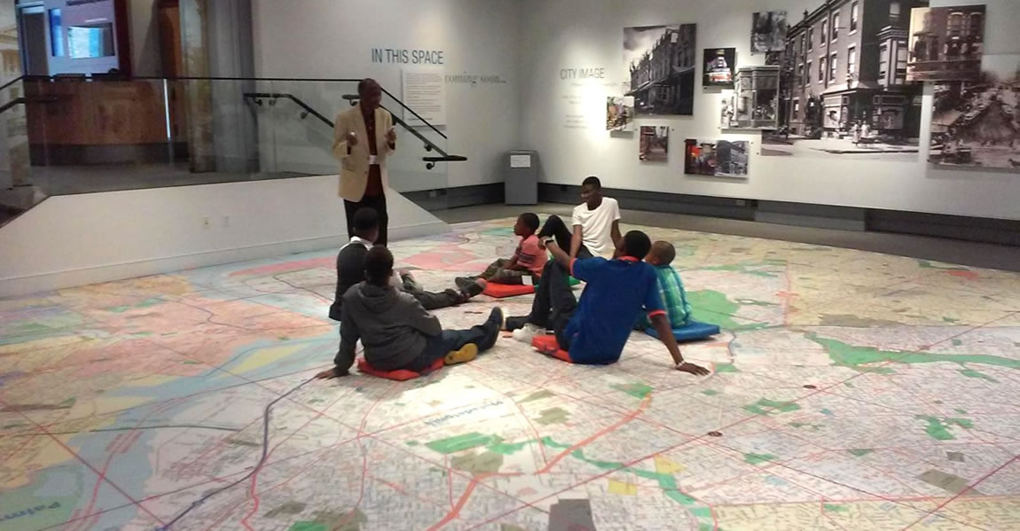 Six young men listen to a museum presentation while seated on a map lined floor