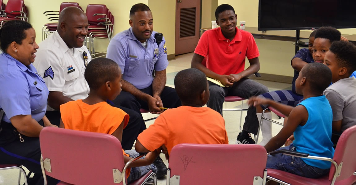 Seven young men sit have a circle discussion with smiling community police officers